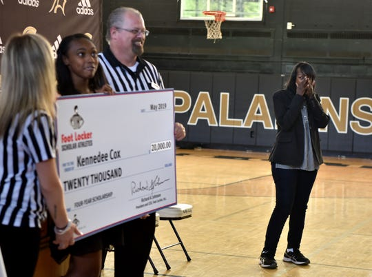 Beverlee Garvin wipes away tears while her daughter, Paramus Catholic senior Kennedee Cox poses for pictures with her $20,000 check from the Foot Locker Scholar Athletes Program. Cox, of Teaneck, runs track at Paramus Catholic. Foot Locker representatives surprised Cox with the announcement at school on Wednesday, May 15, 2019.