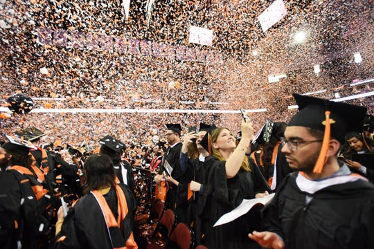 Orange and white confetti falls on the newly graduated, as the ceremony concludes.