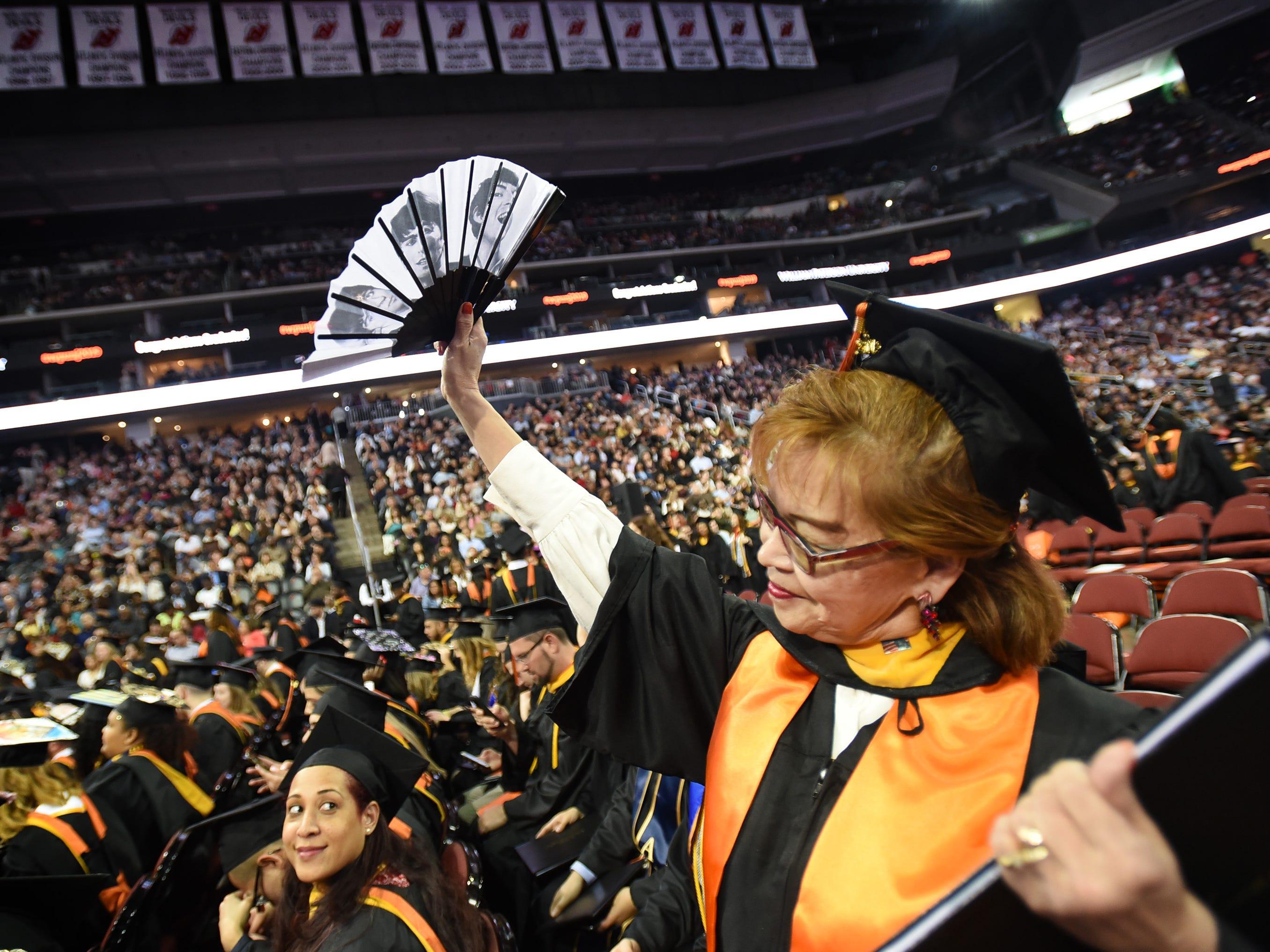 Monica Rieg of Clifton, Major in Business Accounting, waves with a fan that was sent by her son from England, during the William Paterson University 2019 Commencement at the Prudential Center in Newark on 05/15/19.