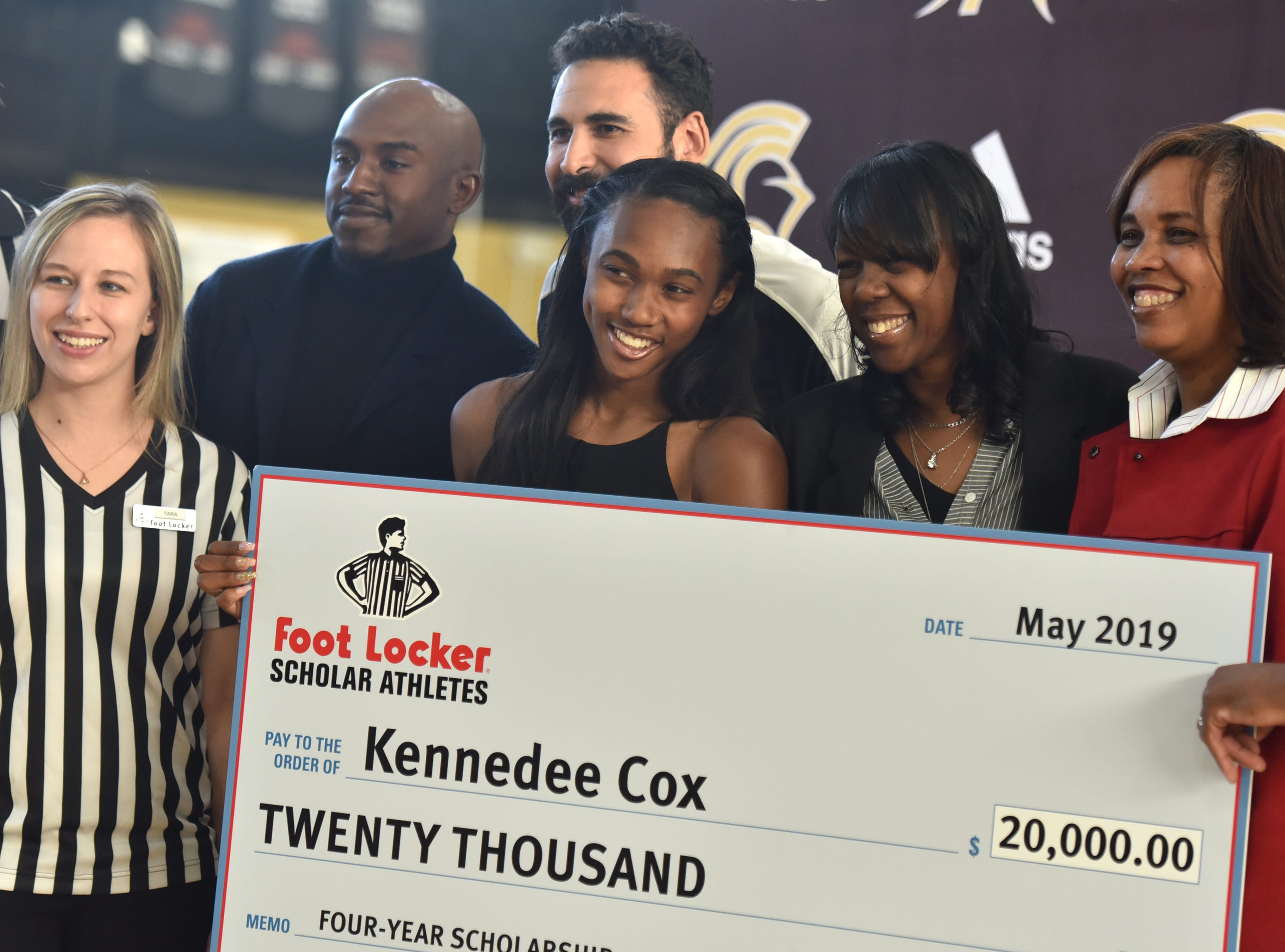 Tara Swett of Foot Locker, Paramus Catholic track coaches Brian Walker and Bryan Durango, Paramus Catholic senior Kennedee Cox, her mother Beverlee Garvin and Cox's aunt Celeste Garvin-Hayes pose for pictures with a $20,000 check Cox received from the Foot Locker Scholar Athletes Program. Foot Locker representatives surprised Cox with the announcement at school on Wednesday, May 15, 2019.