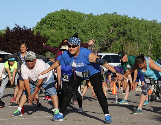 Mina Gray, center, stretches during warm up exercises on May 14 before the start of Just Move It at the San Juan Chapter house in Lower Fruitland.