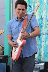 Levi Platero picks out a lead guitar part during a performance with his band Tuesday night in downtown Farmington.