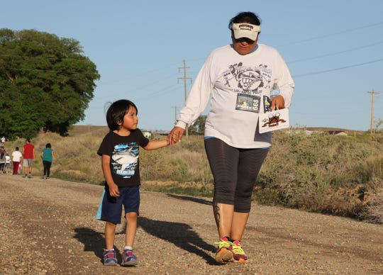 Carmelita Benally and her son, Kade Cadman, walk on Navajo Route 362 on May 14 during Just Move It at the San Juan Chapter in Lower Fruitland.