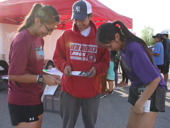 From left, Lauren Bee, Jaisek Bee and Dahliah Bee attach their bib numbers after registering for Just Move It on May 14 at San Juan Chapter house in Lower Fruitland.