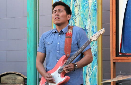 Blues guitarist Levi Platero picks out a lead during a concert with his band Tuesday night in the pocket park behind Studio 116 in downtown Farmington.