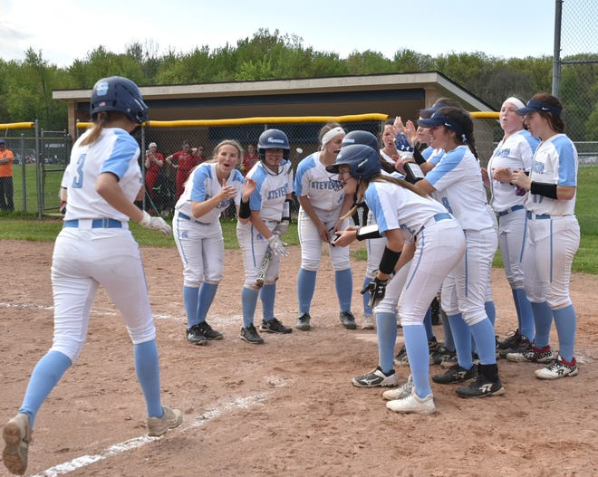 The teammates of Livonia Stevenson Spartan Maddie Schurnack welcome her back to home plate after she launched a solo homerun over the leftfield fence in the sixth inning of their May 15, 2019 game against John Glenn.