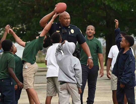 Officef Dwight Brown plays a game of pick-up football with students from Southwest Elementary during Teacher Appreciation Week.