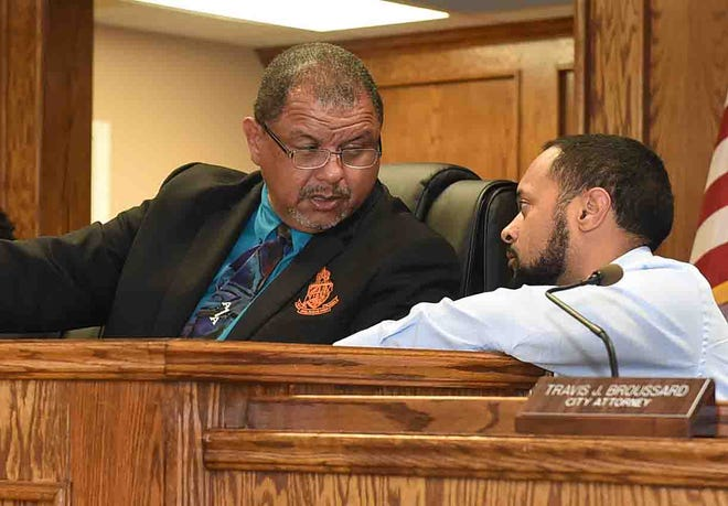 Mayor Julius Alsandor, left, and attorney Travis Broussard discuss the acquisition of the New Life Center building by the city during Tuesday's Board of Aldermen meeting.