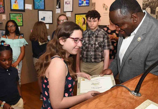 Alderman-At-Large Marvin Richard hands out certificates to area students that participated in the City of Opelousas Art Show held at the Opelousas Museum and Interpretive Center.