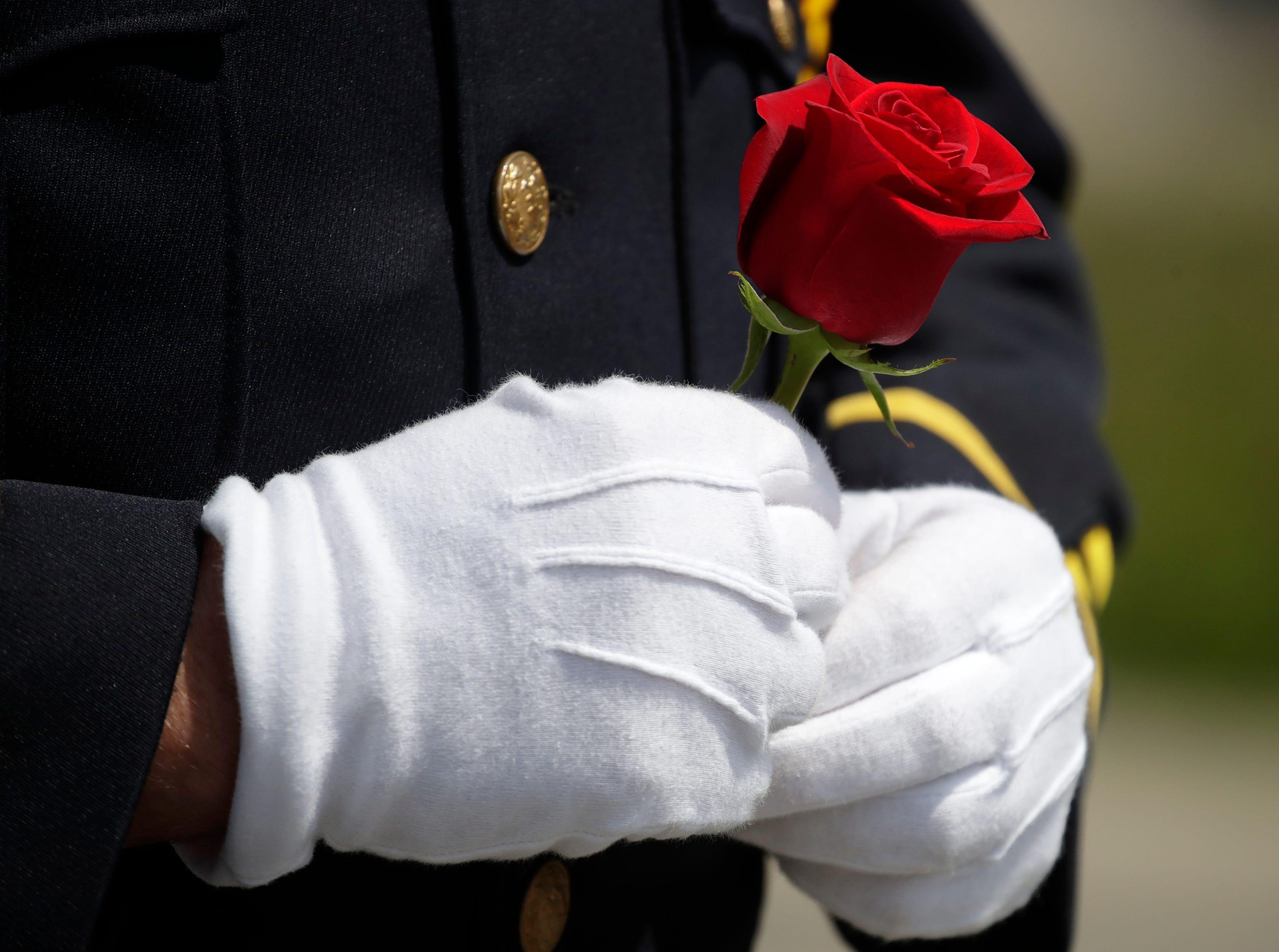 An Oshkosh police officer with the Oshkosh Police Honor Guard holds a rose that he will later place on a wreath in memoriam of an officer that died while on duty during their Law Enforcement Memorial Ceremony Wednesday, May 15, 2019, at the Oshkosh Police Department in Oshkosh, Wis. Danny Damiani/USA TODAY NETWORK-Wisconsin