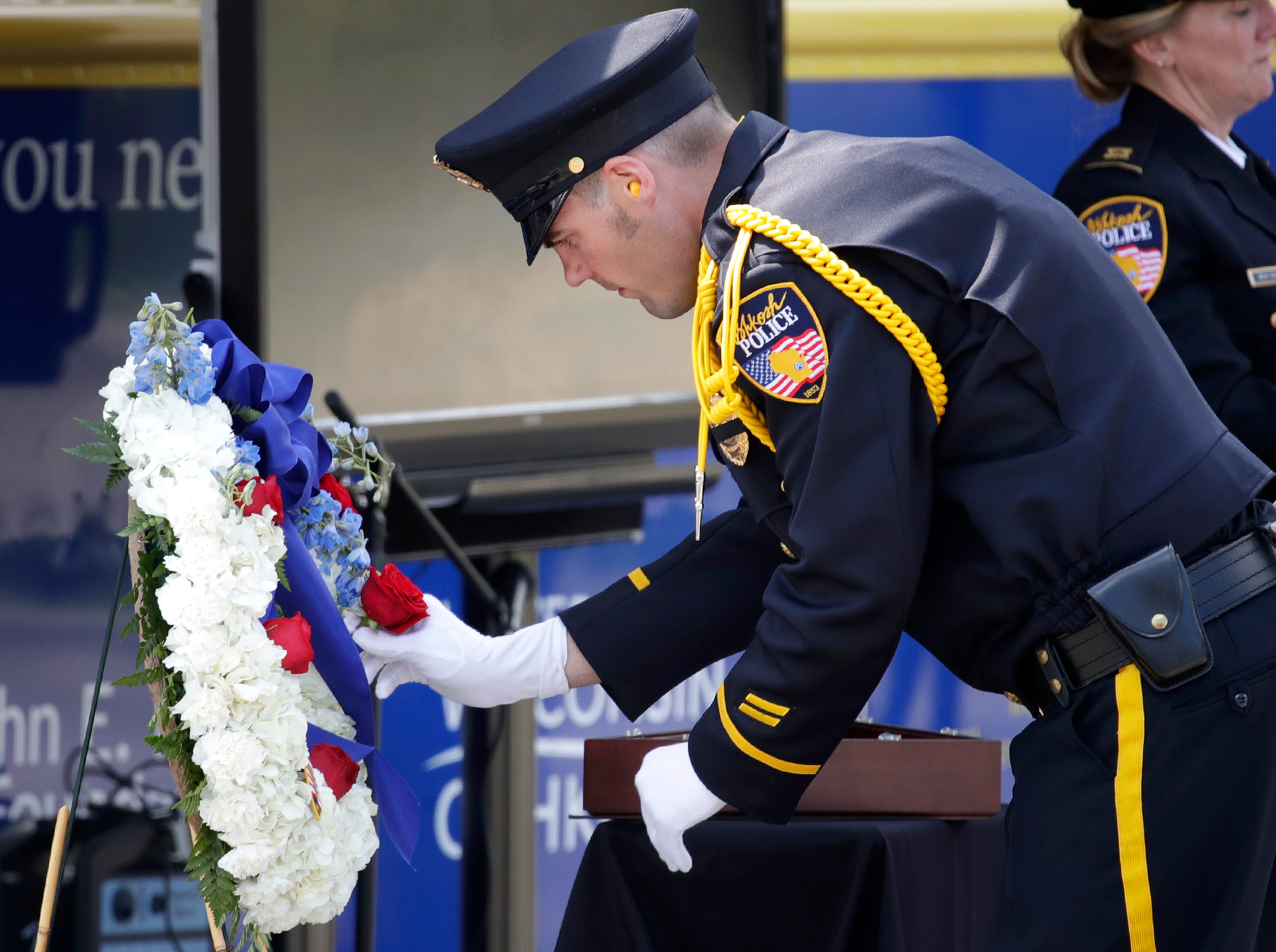 Officer Grant Wilson, with the Oshkosh Police Department, places a rose on a wreath in remembrance of an officer who died while on duty during their Law Enforcement Memorial Ceremony Wednesday, May 15, 2019, at the Oshkosh Police Department in Oshkosh, Wis. Danny Damiani/USA TODAY NETWORK-Wisconsin