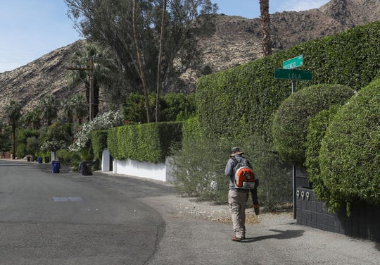 A landscaper uses a gas powered leaf blower to clear leaves from a Palm Springs residence, May 15, 2019.