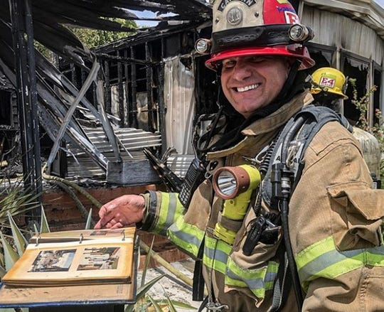 "A Palm Springs firefighter shows off a photo album saved from a mobile home that was destroyed in a fire Wednesday morning. Posted on the Palm Springs Police Department's Instagram account, the caption read, ""Remember when photos were kept in a book? PSFD saved the memories from this structure Fire."""