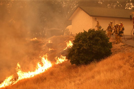 Cal Fire firefighters protect a home in Igo while battling the Carr Fire, on Saturday, July 28, 2018. Insurance rates have risen significantly for homeowners in fire country.