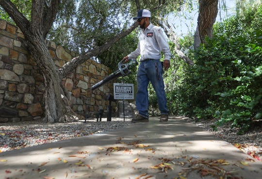 Jose Jacquez with Randy G. Myers & Nurseries uses an electric blower to clear leaves from a Palm Springs residence, May 15, 2019.
