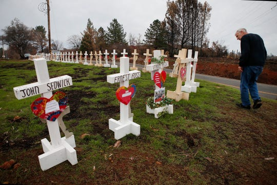 Steve Boese looks for the name of his neighbor among the 86 crosses of Camp Fire victims erected in Paradise. (Karl Mondon/Bay Area News Group)