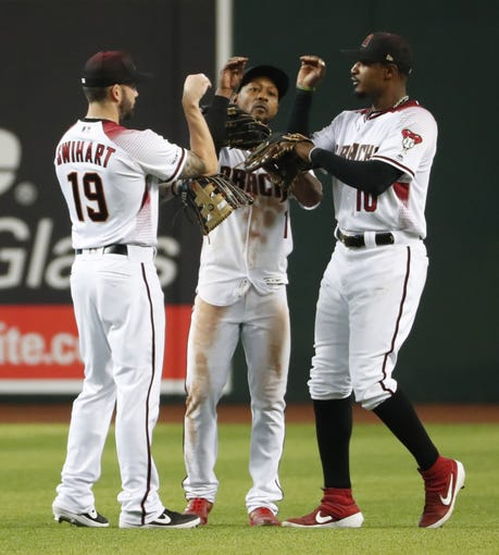 Arizona Diamondbacks outfielders Blake Swihart (19) Jarrod Dyson (1) and Adam Jones (10) celebrate after beating the Pittsburgh Pirates 11-1 at Chase Field in Phoenix, Ariz. May 15, 2019.