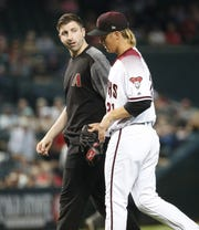 Arizona Diamondbacks starting pitcher Zack Greinke (21) exits the game after an apparent injury after a pitch against the Pittsburgh Pirates as Head Athletic Trainer Ryan DiPanfilo walks with him during the eighth inning at Chase Field in Phoenix, Ariz. May 15, 2019.