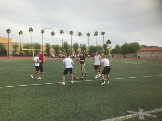 Brophy Prep freshman quarterback, right, goes through drills with teammates.