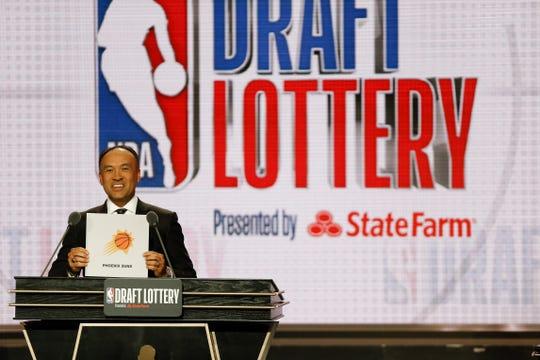 El Comisionado de la NBA Mark Tatum muestra el cartoncillo de Phoenix Suns, que lo acredita como el #6 de la lotería.