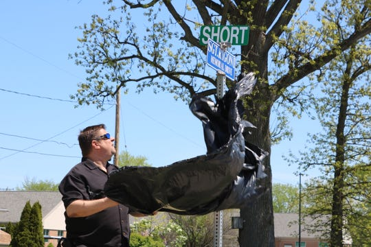 Billy Rigoni, son of the late Sgt. Robert B. Rigoni, who died in a plane crash while responding to an emergency reported on Kelleys Island in 1983, unviels a sign marking the dedication of an eastern portion of 6th Street in his father's honor.