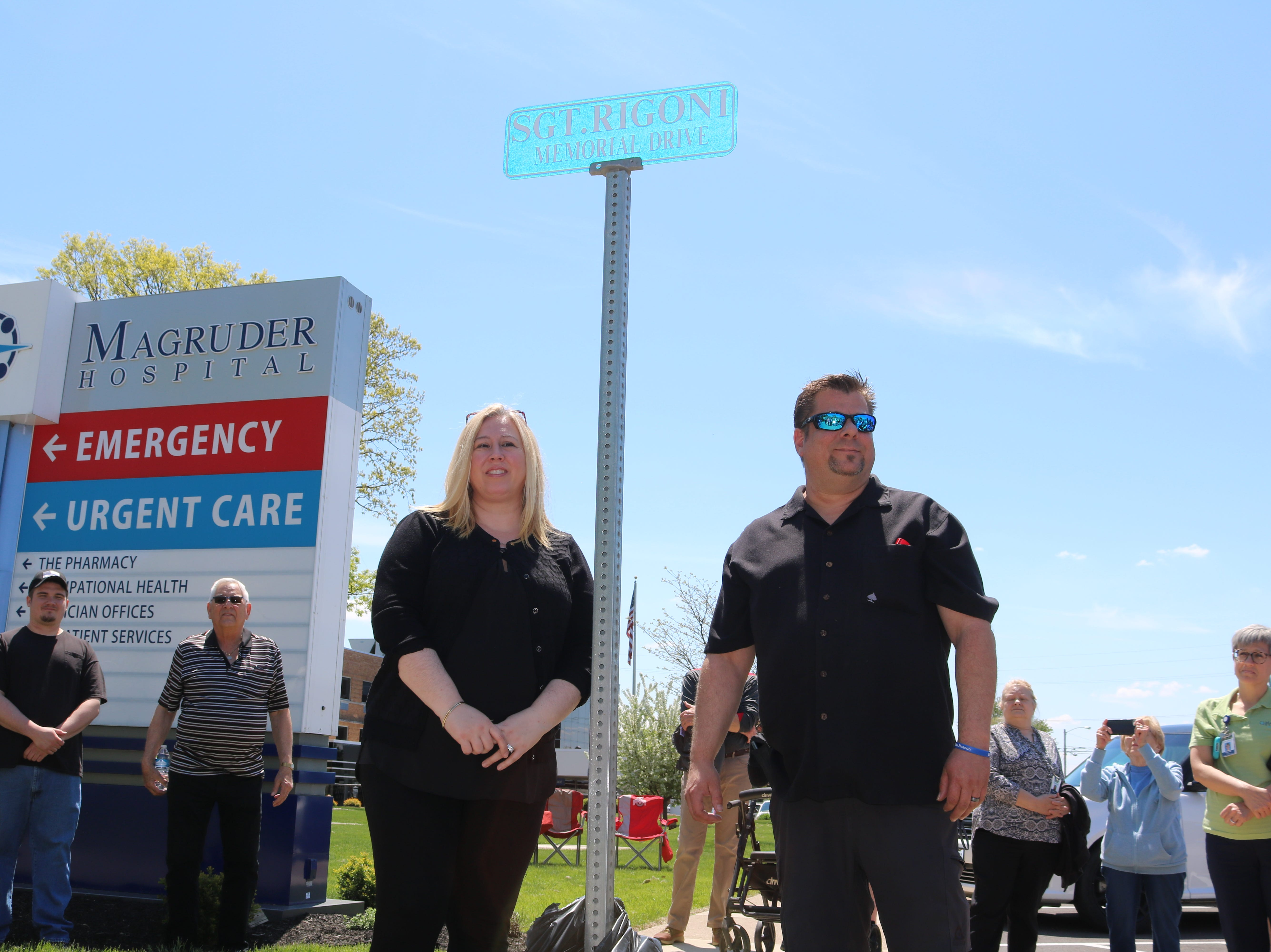 Kelly and Billy Rigoni, son of the late Sgt. Robert B. Rigoni, who died in a plane crash while responding to an emergency reported on Kelleys Island in 1983, stands before the sign marking an eastern portion of 6th Street in his father's honor.