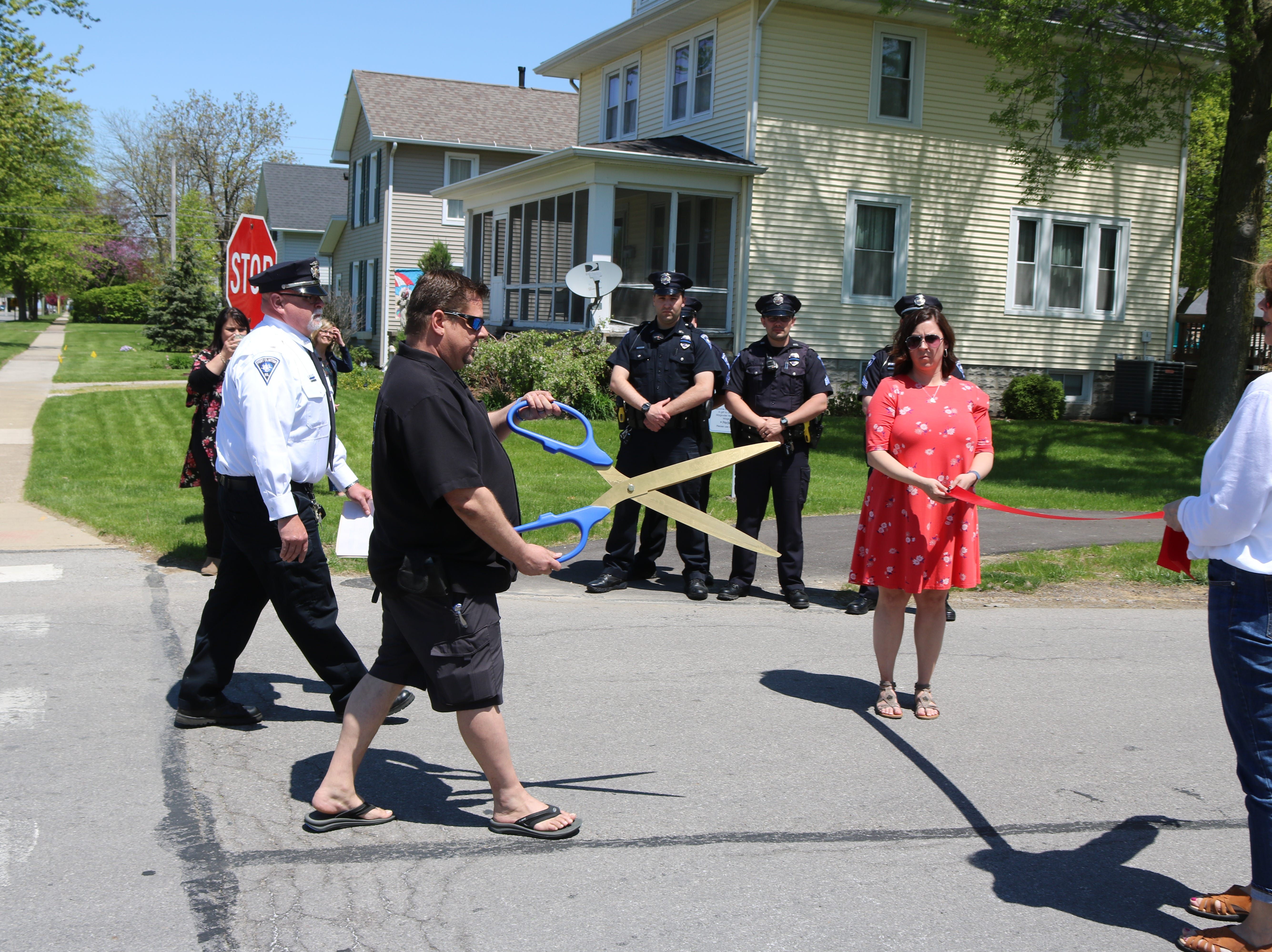Billy Rigoni, son of the late Sgt. Robert B. Rigoni, who died in a plane crash while responding to an emergency reported on Kelleys Island in 1983, prepares to cut the ribbon dedicating an eastern portion of 6th Street in his father's honor.