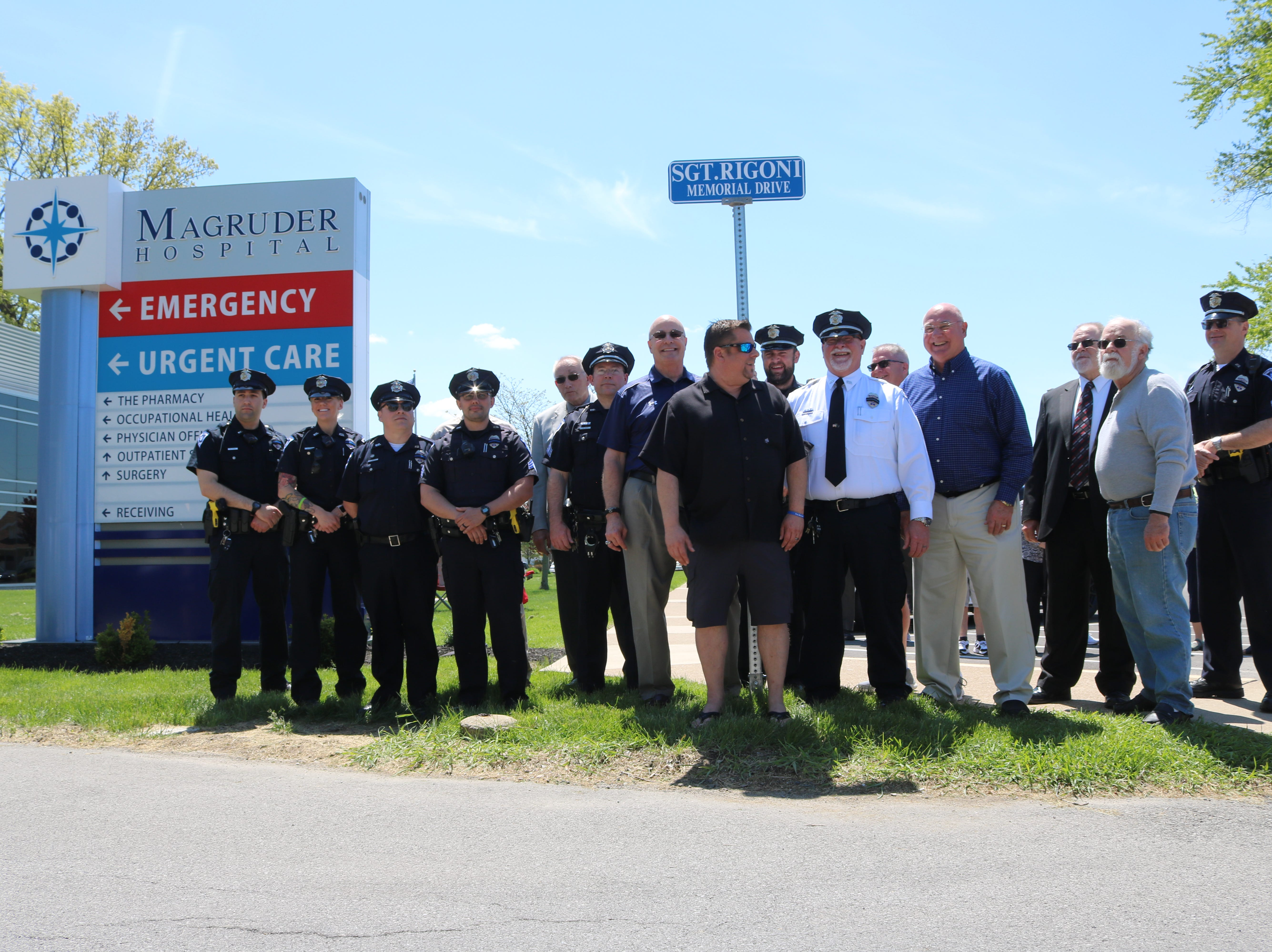 Kelly and Billy Rigoni, son of the late Sgt. Robert B. Rigoni, who died in a plane crash while responding to an emergency reported on Kelleys Island in 1983, stands with former police officers before the sign marking an eastern portion of 6th Street in his father's honor.