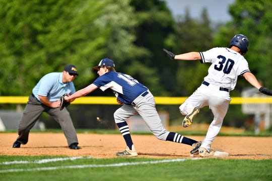 Dallastown's Peyton Fox, left, catches the ball at first to out West York's Seth Eyler during baseball semifinal action at Spring Grove Area High School in Jackson Township, Wednesday, May 15, 2019. Dallastown would win the game 12-0. Dawn J. Sagert photo