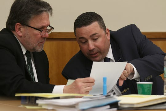 Defense attorney Clark Zimmermann goes over photos with Officer Michael Sippel the prosecutor wants to introduce into evidence.