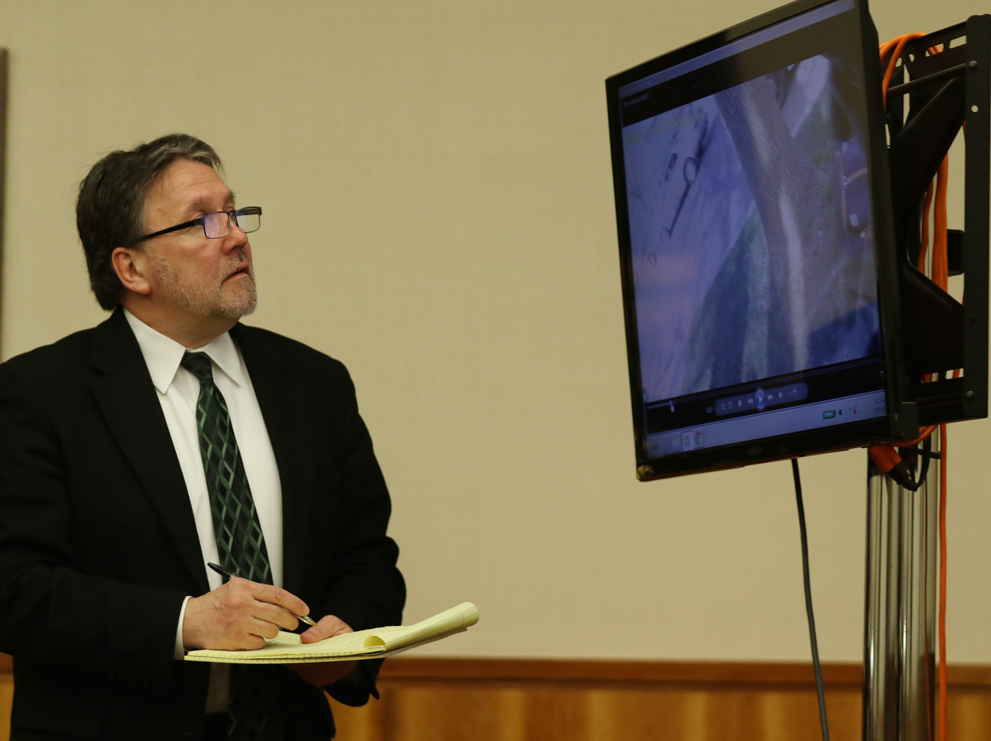Defense attorney Clark Zimmermann looks for the time stamp on the video footage for scenes he objected to.
