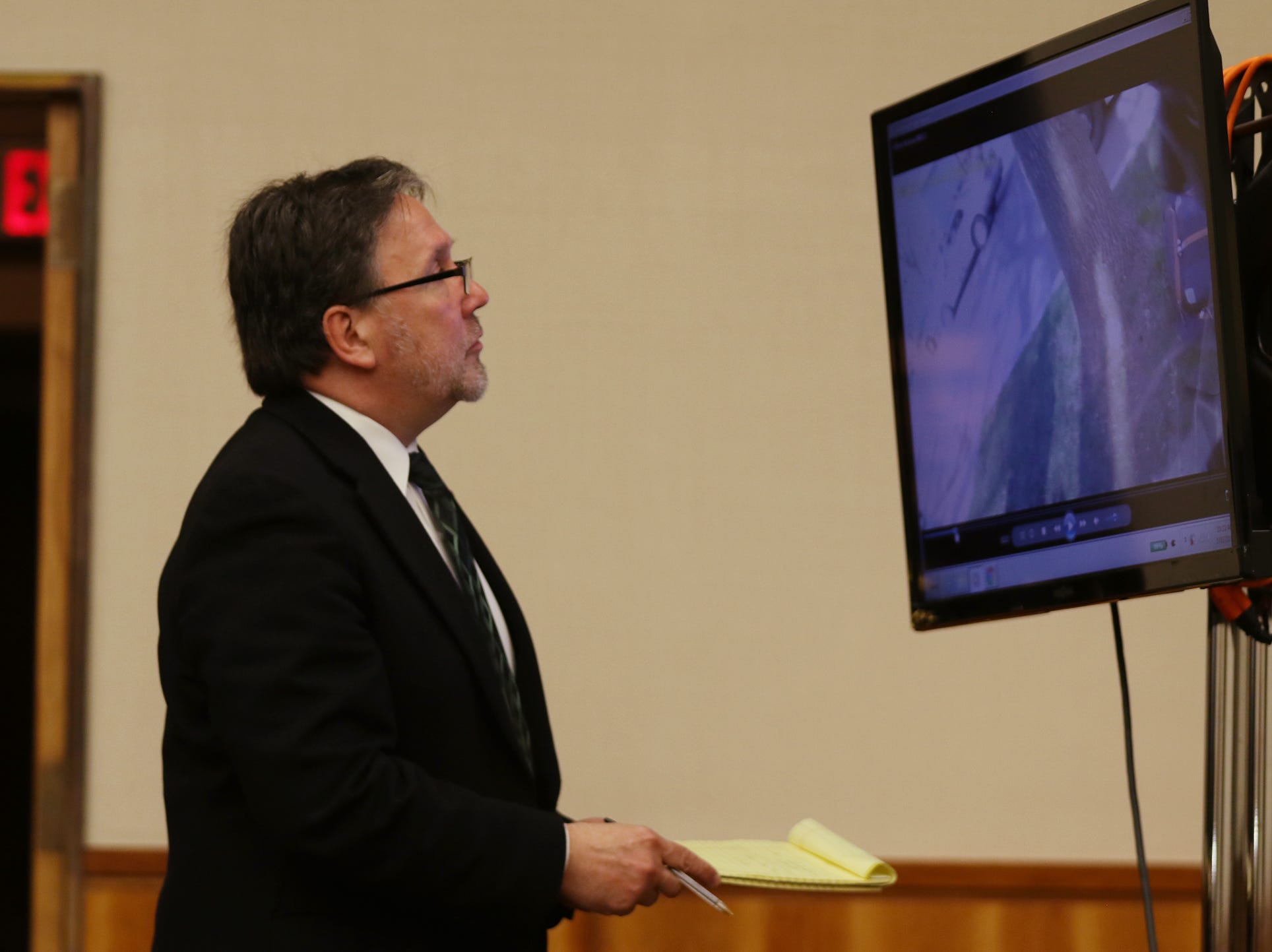 Defense attorney Clark Zimmermann looks for a time stamp on a video for scenes he objected to.