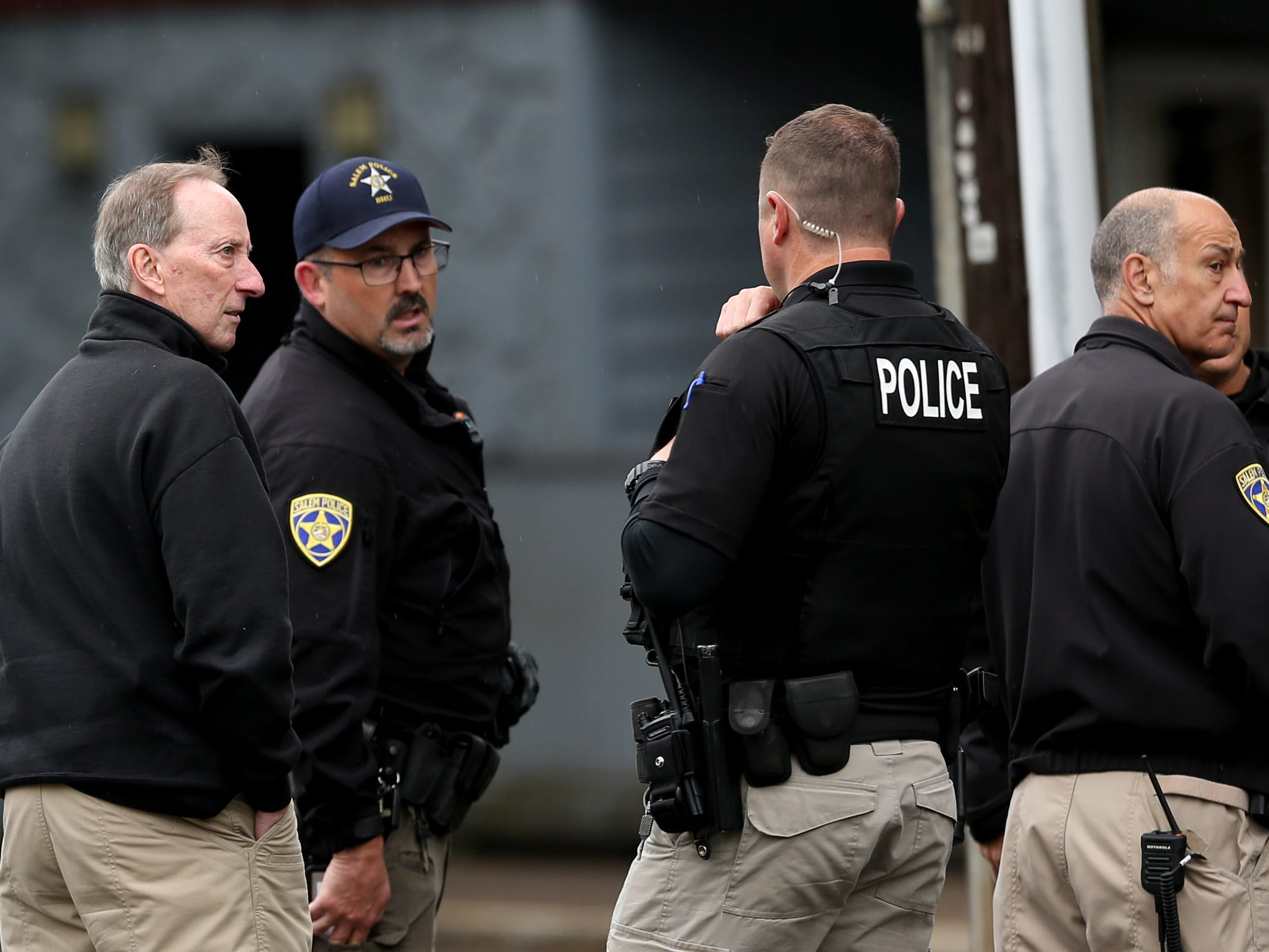 Salem Police Chief Jerry Moore, far left, and others respond to an apartment where a suspect in an overnight officer-involved shooting was hiding out on Broadway St. NE in Salem on May 15, 2019. Following a traffic stop on Tuesday evening, a veteran Salem Police patrol officer was wounded by multiple gunshots. She has since been released from Salem Hospital. Police also took another person into custody who was in the apartment.