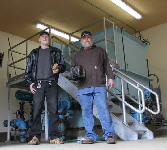 Idanha city councilor Jeff Yohe (left) and public works director Bob Bruce (right) stand in front of the city's sand water filter, which will be replaced by a more advanced membrane water filtration system.
