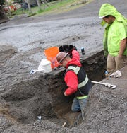 Workers install a new water line to a house as part of the city's new water distribution system.
