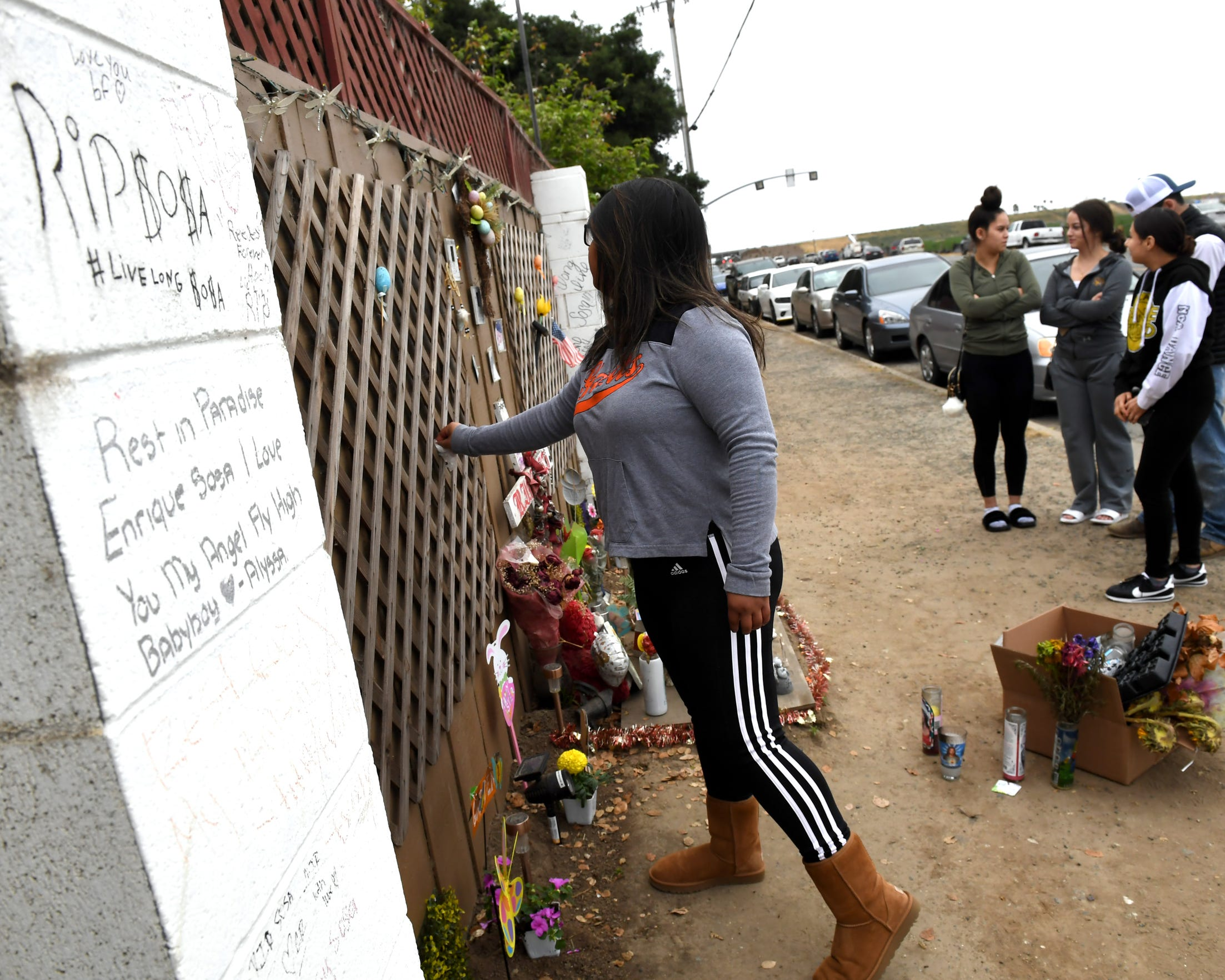 "Enrique ""Kiki"" Sosa, 14, was shot and killed on Russell Road in January 2017. His sister Cecily Rodriguez (left) tends to his memorial in  May 2019. Friends stand nearby."