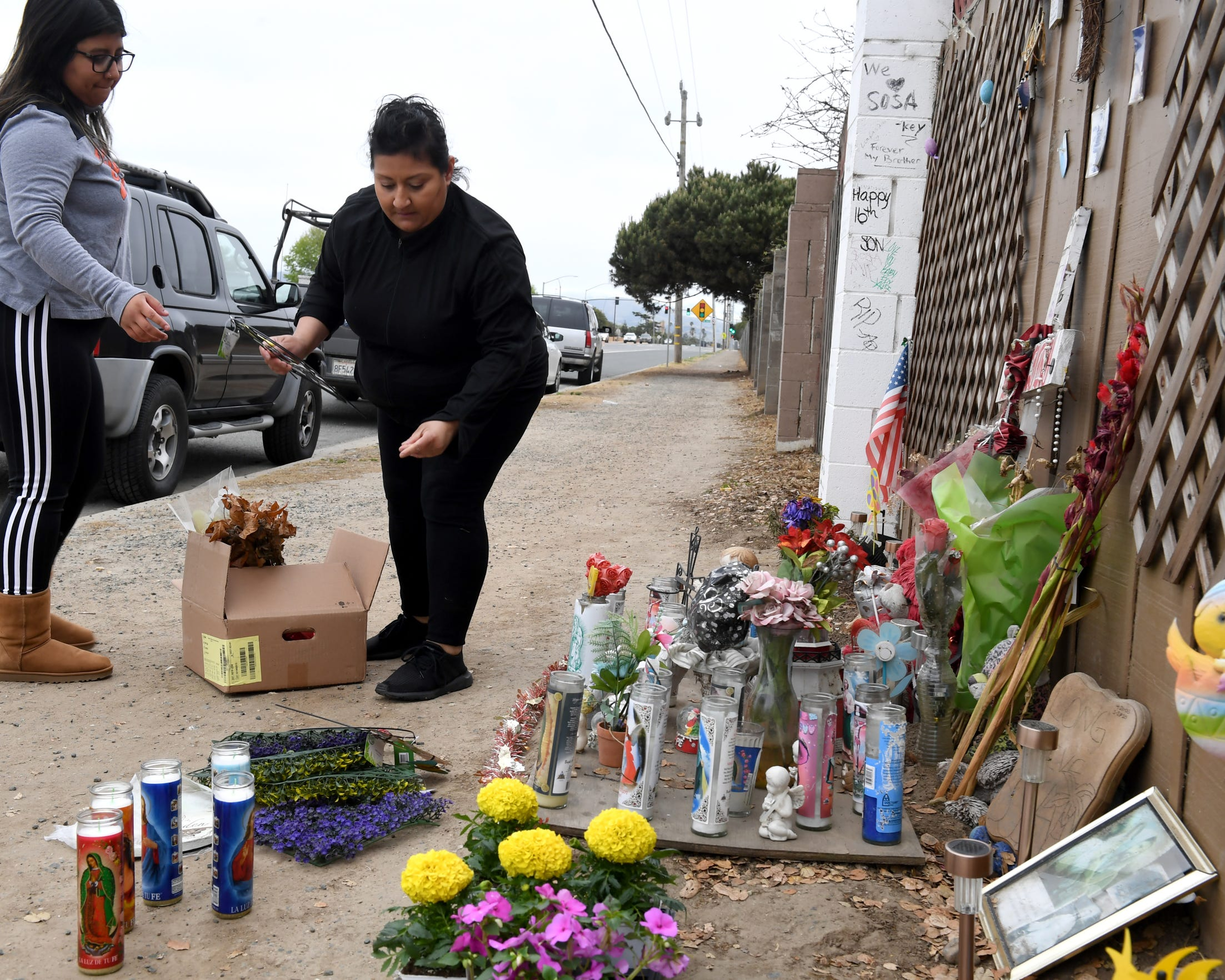 "Enrique ""Kiki"" Sosa, 14, was shot and killed on Russell Road in January 2017. His mother Lenore Sosa (right) and sister Cecily Rodriguez (left) tend to his memorial in  May 2019."