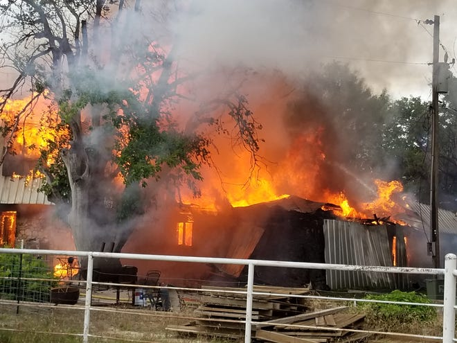 Flames engulf a house at 7465 FM 765 Monday, May 13, 2019.
