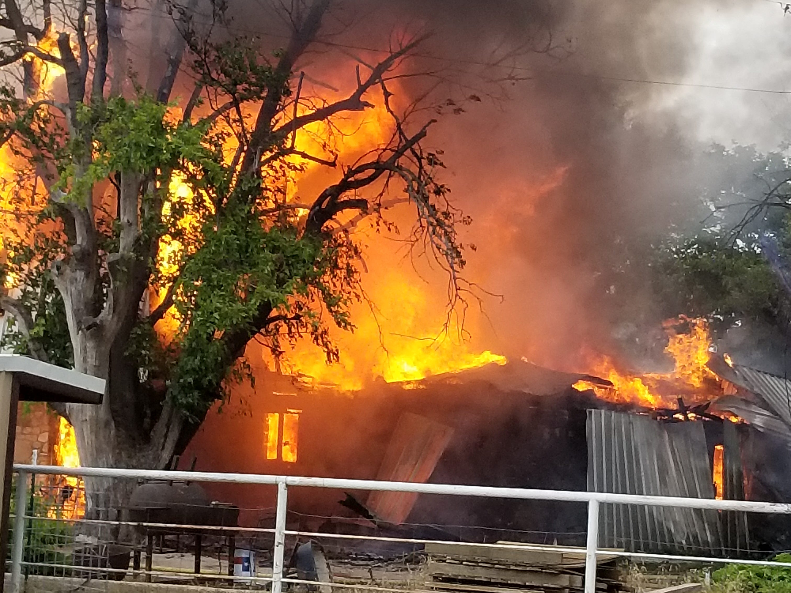 A house at 7465 FM 765 begins to fall after catching on fire Monday, May 13, 2019.