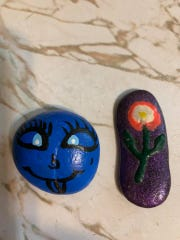 One rock is painted blue with a face and the other is painted purple with a flower. Both were hidden in San Angelo.