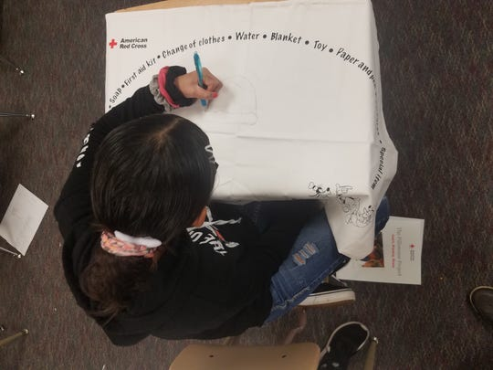A Grant Elementary student decorates a disaster-preparedness pillow case.