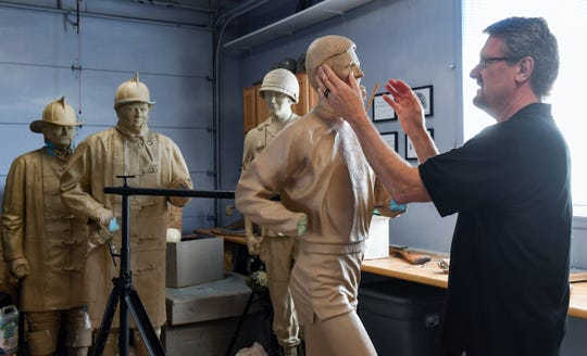 Darwin Wolf sculpts a full-size likeness of late cross country coach Rich Greeno in his home studio Tuesday, May 14, in Sioux Falls. Works-in-progress of firefighter and soldier memorials stand just behind.