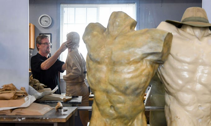 Darwin Wolf sculpts a work-in-progress in his home studio Tuesday, May 14, in Sioux Falls. The sculpture, made of foam and clay, will act as the mold for a bronze cast.