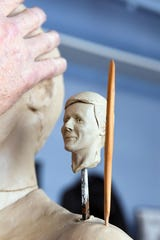 A miniature sculpted head of late cross country coach Rich Greeno sits in the shoulder of the full-size sculpture to give Darwin Wolf a point of reference in his home studio Tuesday, May 14, in Sioux Falls.