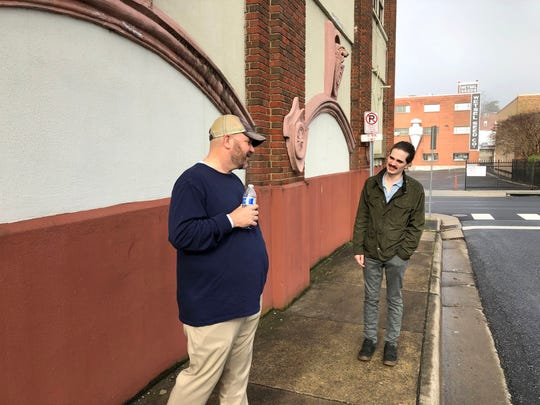 Jarrett Hatcher talks with fellow comedian Christopher Cantrell on the sidewalk outside of Harrisonburg's Court Square Theater.