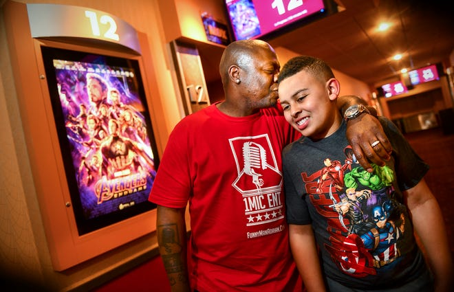 "Local comedian Adrian Washington embraces his son Masyn in front of a theatre where ""Avengers: Endgame"" is playing Wednesday, May 15, at Marcus Parkwood Cinema in Waite Park. Washington is sponsoring a free screening of the movie for people of all ages who have developmental disorders or other disabilities Sunday."