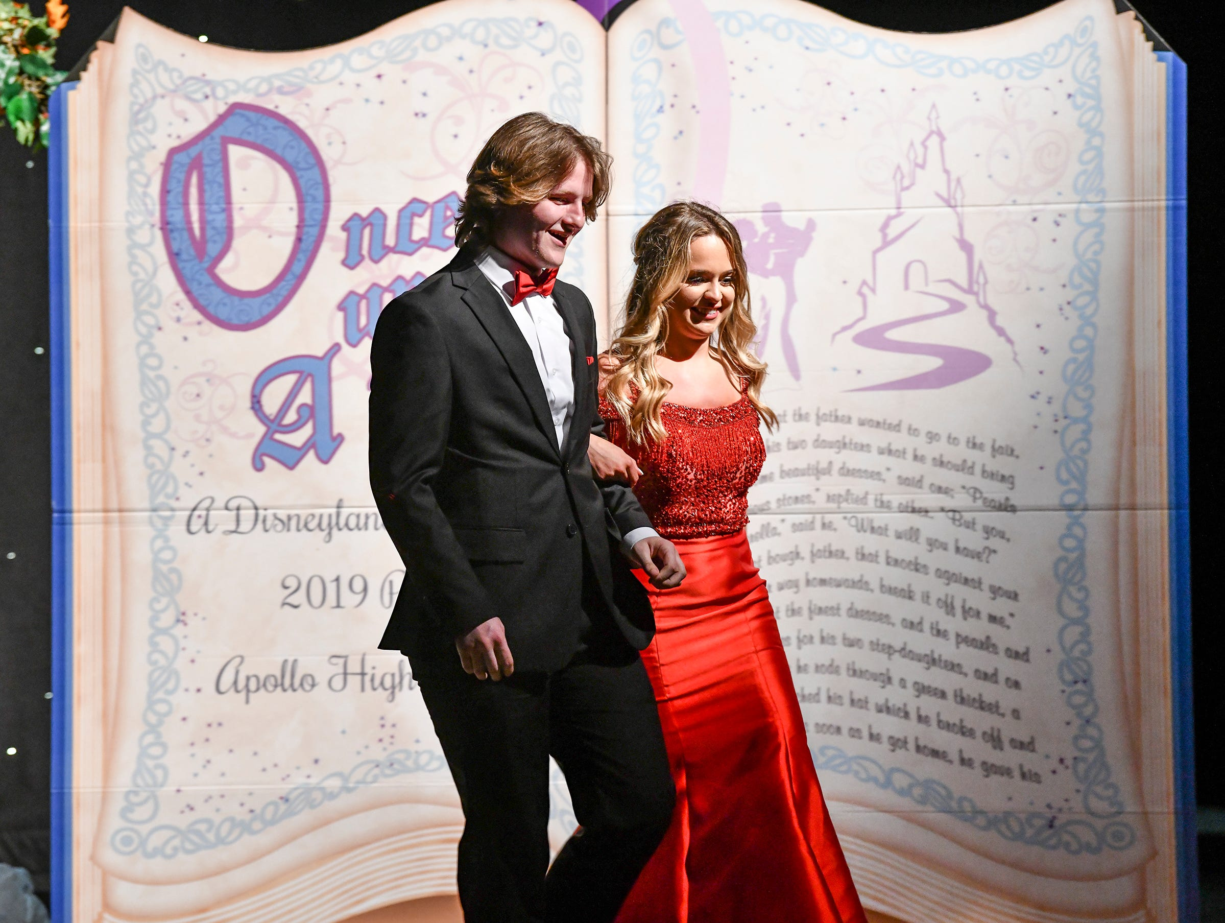 A couple makes their way across Disney-themed stage decorations during prom grand march Saturday, May 11, at Apollo High School in St. Cloud.