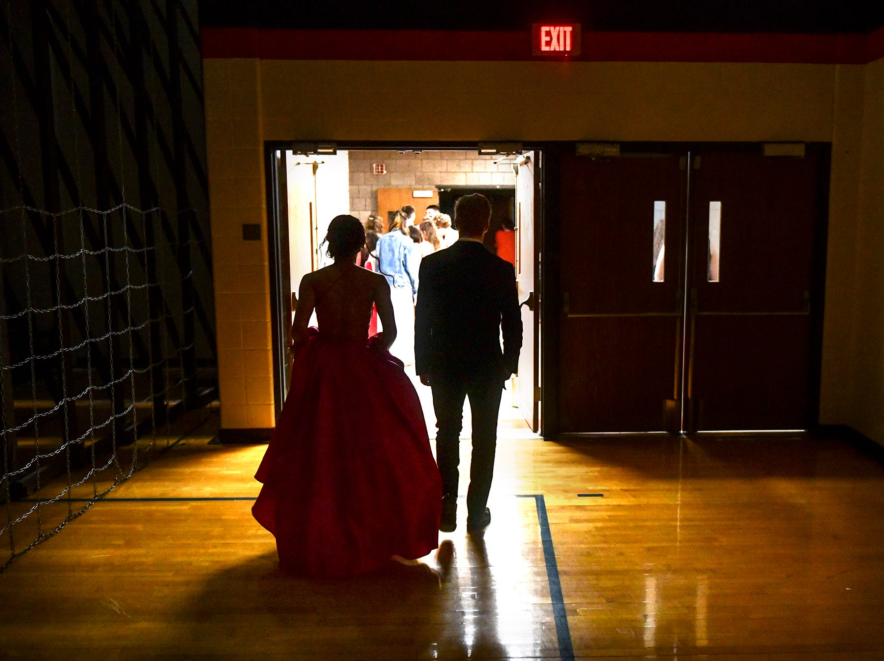 A couple leaves the Tech High School gym following prom grand march Saturday, April 27, at Tech High School in St. Cloud. This was the last prom held in the current gym at Tech.
