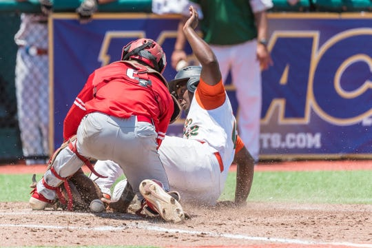 Kaycee Reese slides safely at home as Delaware State catcher Adrian Hill loses the ball. The Rattlers beat the Hornets 13-3 to advance to the second round of the MEAC Baseball Championship at Jackie Robinson Ballpark in Daytona Beach.