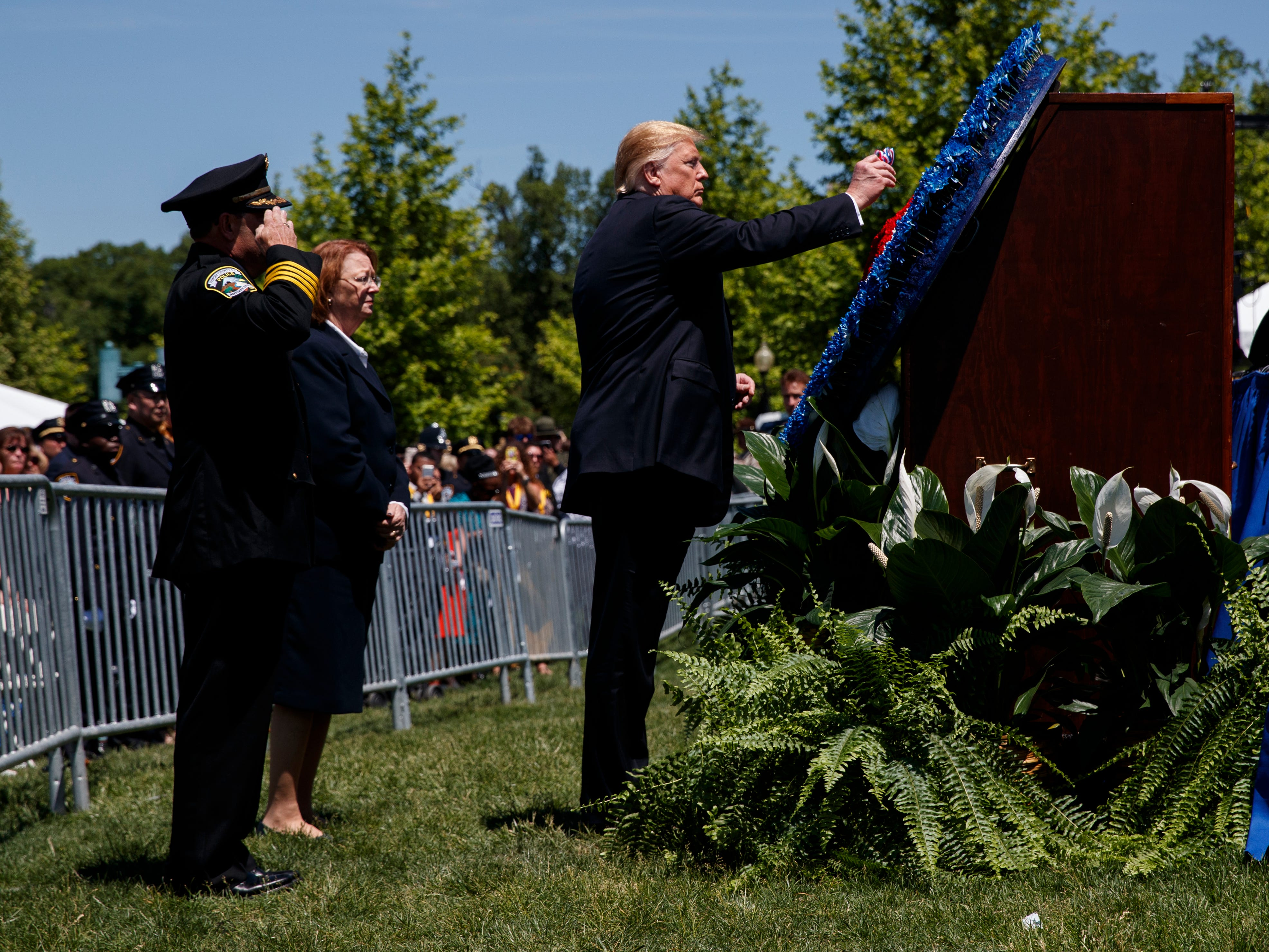 President Donald Trump places a flower in a wreath during the 38th Annual National Peace Officers' Memorial Service at the U.S. Capitol, Wednesday, May 15, 2019, in Washington.
